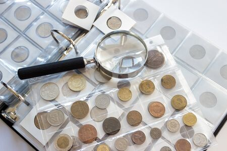 Foto de Different old collector's coins with a magnifying glass, soft focus - Imagen libre de derechos