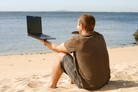 man working with computer at beach