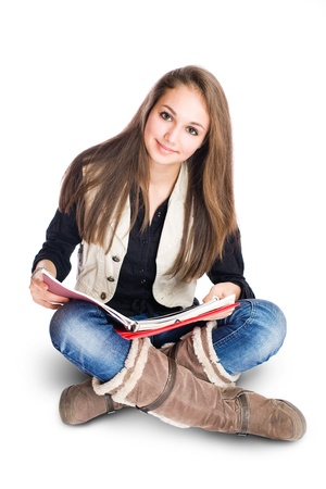 Portrait of a beautiful cute young student girl sitting and reading.