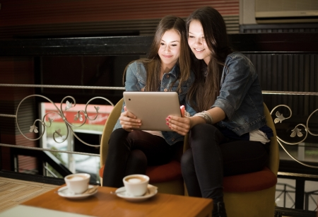 Two beautiful young girls sharing tablet computer