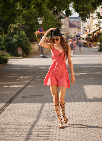 Gorgeous brunette model woman outdoors wearing pink summer dress.