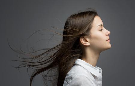 Foto de Portrait of a young dreamy brunette beauty with windswept hair. - Imagen libre de derechos