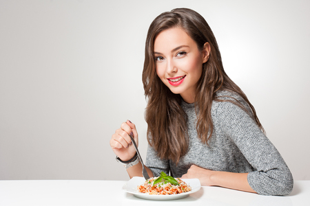 Foto per Beautiful young brunette woman eating Italian pasta. - Immagine Royalty Free