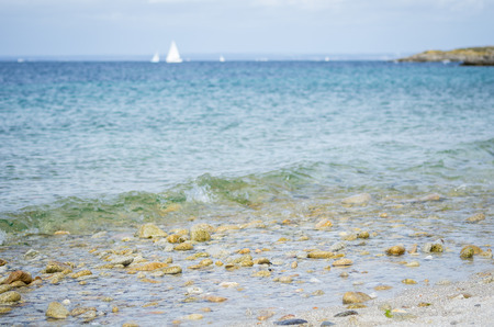 Foto de Pebble beach, with blue sea and white boat in the background. Photographed in Glenan Isles (France) - Imagen libre de derechos