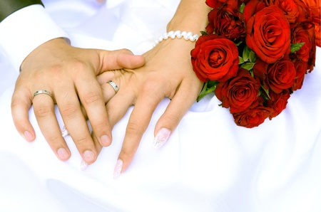 Photo for Bride and groom holding hands and a bouquet of red roses - Royalty Free Image