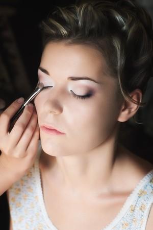 Makeup artist applying eye shadow on beautiful young woman with selective focus