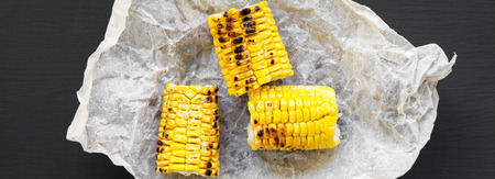 Foto per Grilled corn on the cob over black background, overhead view. Summer food. Top view, flat lay. Close-up. - Immagine Royalty Free