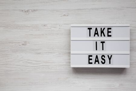 Photo pour 'Take it easy' words on a modern board on a white wooden surface, top view. Overhead, from above, flat lay. Copy space. - image libre de droit