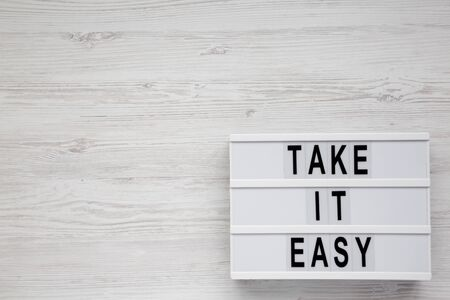 Photo pour 'Take it easy' words on a modern board on a white wooden background, top view. Overhead, from above, flat lay. Copy space. - image libre de droit