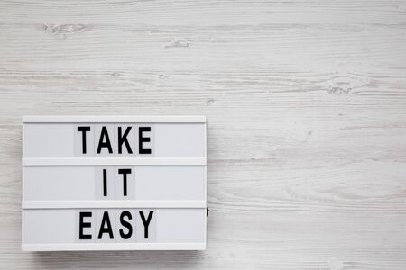 Photo pour 'Take it easy' words on a lightbox on a white wooden surface, top view. Overhead, from above, flat lay. Space for text. - image libre de droit