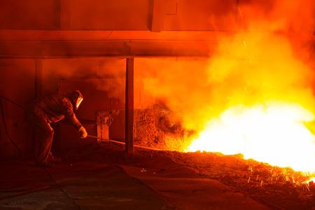 iron works blast furnace taphole spewing molten iron, closeup of photo
