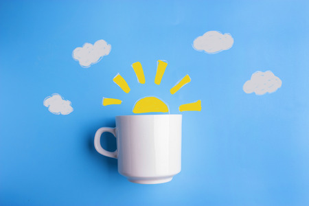 Foto de sun and white cup on blue background. good morning concept - Imagen libre de derechos