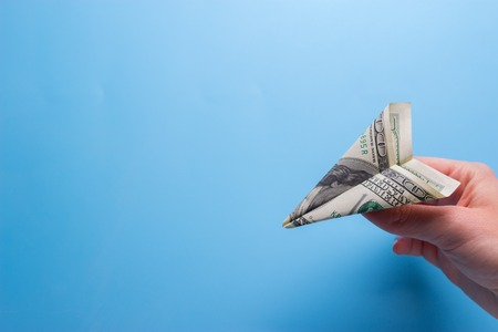 Photo pour Flying paper plane with dollar banknote holding in hand - image libre de droit