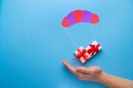 Photo pour beautiful gift box falling down with parachute - image libre de droit