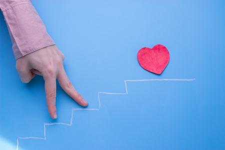 Photo pour heart on the stairs. hand go up the stairs - image libre de droit