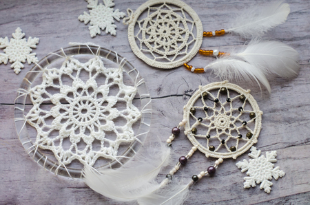 Photo for Dreamcatcher with feathers on a wooden background. Ethnic design, boho style, tribal symbol.White Christmas and New Year snowflake on a wooden vintage old background. - Royalty Free Image