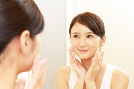 Asian woman looking at her face in mirror