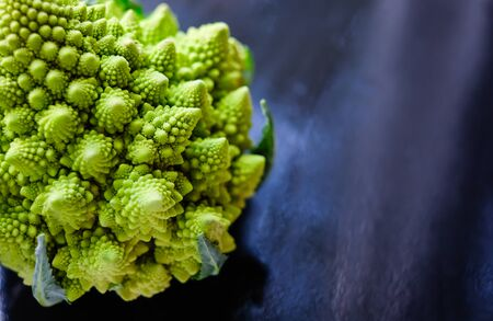 Photo pour Close up view of amazing Romanesco broccoli or Roman cauliflower on wet dark blue background. Its form is a natural approximation of a fractal. - image libre de droit