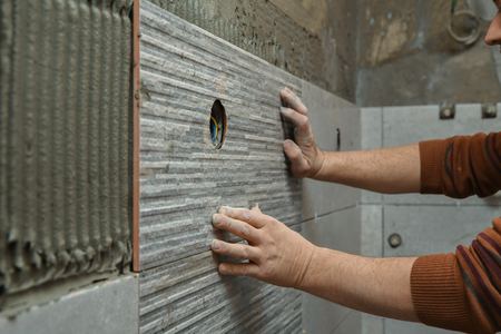 Photo pour Gluing tiles on the wall. Laying tiles on the wall.  Worker installing big ceramic tiles on the walls - image libre de droit