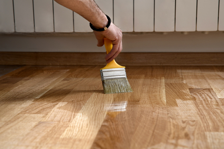 Foto de Varnishing lacquering parquet floor by paintbrush - second layer. Home renovation parquet. Varnish paintbrush strokes on a wooden parquet. Application of a highly glossy parquet lacquer - Imagen libre de derechos