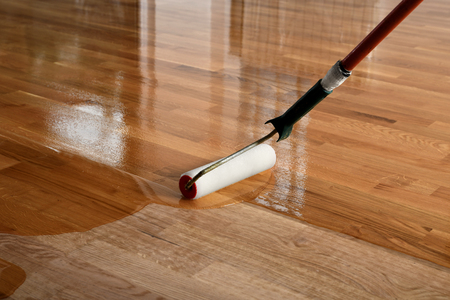 Photo pour Lacquering wood floors. Worker uses a roller to coating floors. Varnishing lacquering parquet floor by paint roller - second layer. Home renovation parquet - image libre de droit