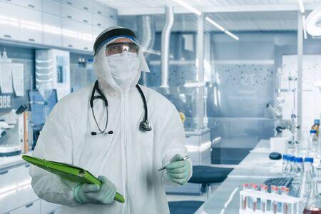 Foto de COVID-19, Corona Virus or Novel coronavirus epidemic disease with doctor or lab technician scientist in PPE Personal Protective Equipment holding preventive plan in hospital laboratory - Imagen libre de derechos