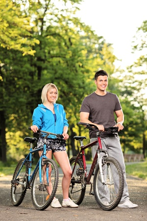 Happy smiling couple with bikes posing in the park