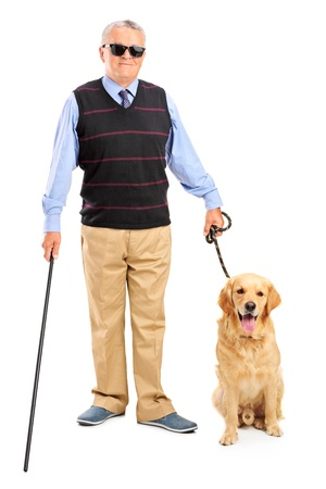 Full length portrait of a blind person holding a walking stick and a dog isolated on white background