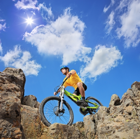 Person riding a mountain bike a mid rocks on a sunny day against a blue sky and clouds, low angle view