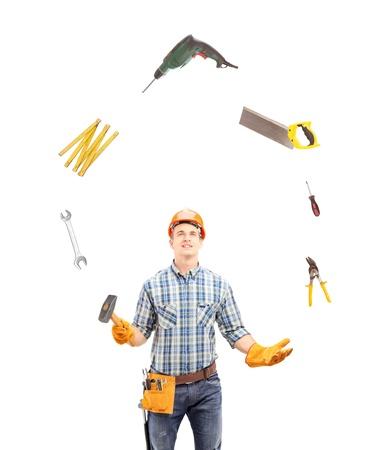 Foto de Manual worker juggling with tools, isolated on white background - Imagen libre de derechos