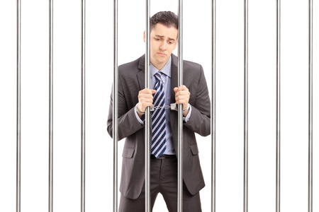 Photo for Handcuffed businessman in suit posing in jail and holding bars, isolated on white background - Royalty Free Image
