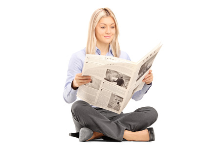 Photo pour Young smiling woman sittong on a floor and reading a newspaper isolated on white background  - image libre de droit