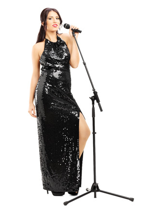 Photo for Full length portrait of a young female singer in black dress posing isolated on white  - Royalty Free Image