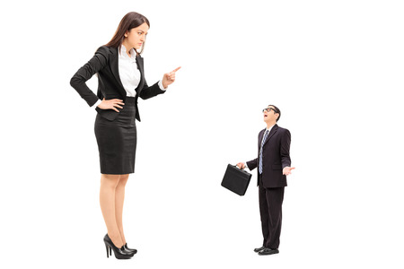 Foto de Giant woman threatening a tiny businessman isolated on white background - Imagen libre de derechos