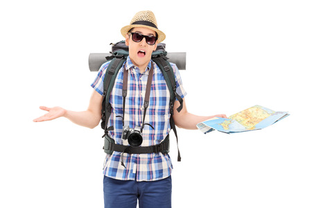 Photo for Lost male tourist holding a map and gesturing with hands isolated on white background - Royalty Free Image