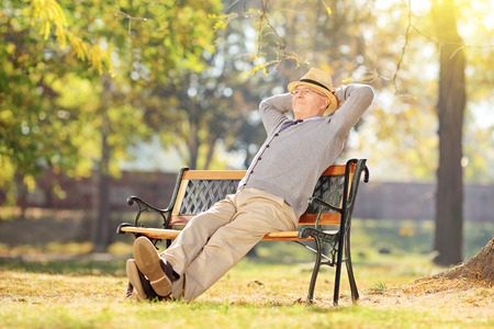 Photo pour Senior man relaxing in park on a sunny day seated on a wooden bench - image libre de droit