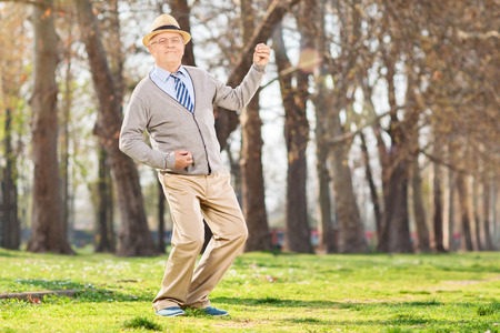 Photo for Senior man playing air guitar in the park - Royalty Free Image