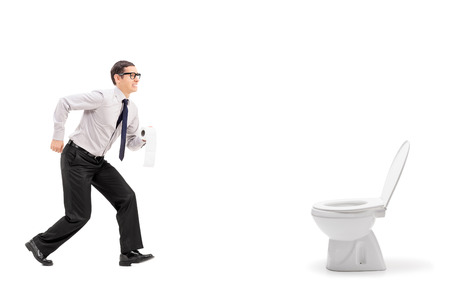 Foto de Man rushing to a urinal and holding toilet paper isolated on white  - Imagen libre de derechos