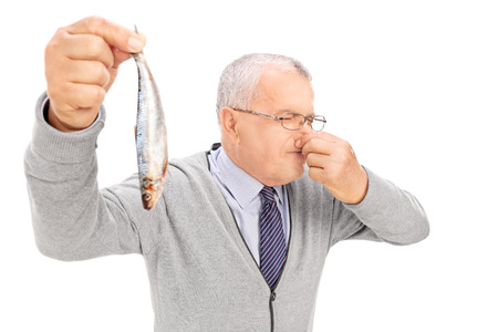Photo for Senior gentleman holding a rotten fish isolated on white background - Royalty Free Image