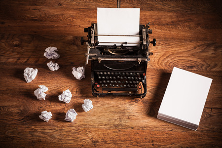 Photo pour Retro typewriter on a wooden desk and a stack of paper beside it - image libre de droit