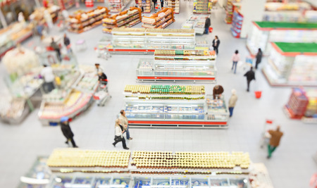 Foto für People shopping in a large supermarket shot with a tilt and shift lens with the focus on the racks   - Lizenzfreies Bild