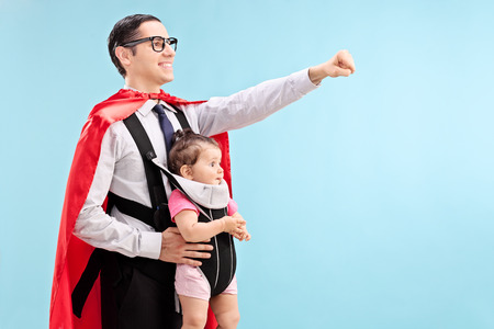 Foto de Proud father in superhero costume carrying his daughter with raised fist on blue background - Imagen libre de derechos