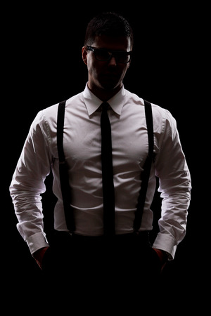 Photo pour Vertical shot of a mysterious man standing in the dark on black background - image libre de droit