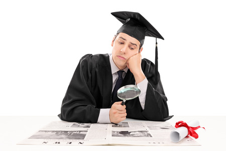 Foto de Graduate student searching for job in the papers isolated on white background - Imagen libre de derechos