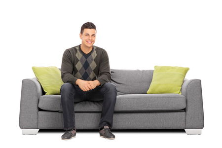 Photo pour Cheerful young man sitting on a modern sofa isolated on white background - image libre de droit
