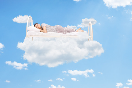 Photo pour Man sleeping on a bed in the clouds high up in the sky - image libre de droit