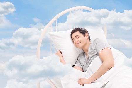 Photo pour Joyful man sleeping on a bed in the clouds - image libre de droit