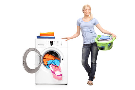Foto per Full length portrait of a young woman holding a laundry basket full of folded clothes and posing next to a washing machine isolated on white background - Immagine Royalty Free