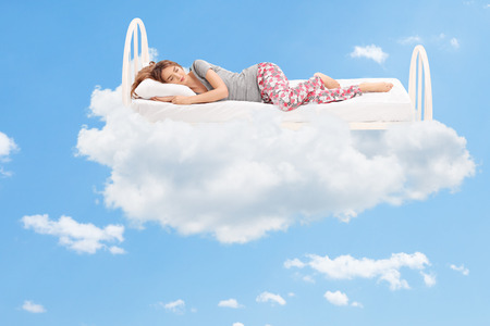 Foto de Relaxed young woman sleeping on a comfortable bed in the clouds - Imagen libre de derechos