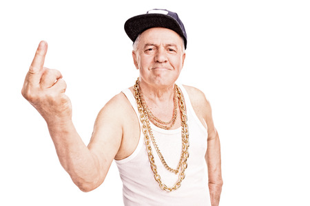 Photo pour Senior man with a hip-hop cap and a golden chain, giving the finger and looking at the camera isolated on white background - image libre de droit
